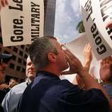 An unidentified Democratic protestor, center, is surrounded by Republican demonstarors as he shouts anti-Republican chants during Senator Bob Dole's speech in front of the Broward County Courthouse in downtown Fort Lauderdale Friday, November 24, 2000. The Broward County Canvassing Board continues its recount of ballots from the still undecided presidential election upstairs. (AP Photo/ Lynsey Addario)  HOUCHRON CAPTION (11/25/2000):  An unidentified Democrat, center, heckles former Sen. Bob Dole as he speaks Friday in front of the Broward County, Fla., Courthouse, where votes are still being recounted. The man is surrounded by Republicans in town to protest the recount.
