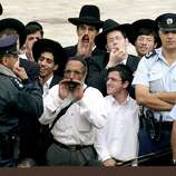 Ultra-Orthodox Jews heckle women praying at the Western Wall in Jerusalem's Old City Sunday June 4, 2000, as Police Commander Yair Yitzhaki, right, looks on.  Dozens of Jewish women, some draped in prayer shawls, prayed out loud at the Western Wall Sunday, defying a bill that would sentence them to seven years in prison.   (AP Photo/Elizabeth Dalziel)
