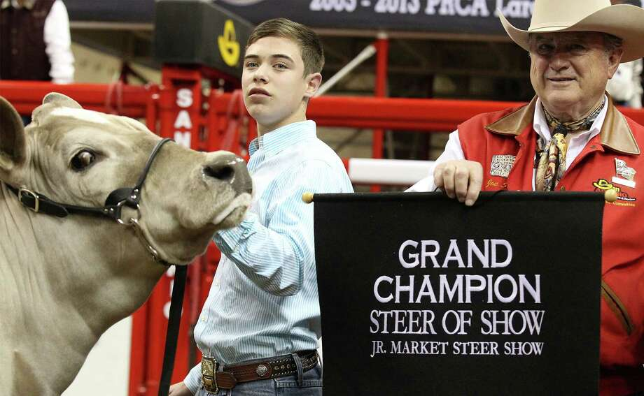 San Antonio Stockshow & Rodeo chairman Joe Soules brings out the grand champion banner for Braeden Brooks Raub of Lampasas FFA and his All Other Breeds (AOB) steer, Beaner, that took the top prize at the Grand Champion Steer judging at the 2014 San Antonio Stockshow & Rodeo at the AT&T Center on Friday, Feb. 21, 2014. Beaver was selected as the grand champion winner over 1,419 other animals in this year's competition. Photo: Kin Man Hui, San Antonio Express-News / ©2013 San Antonio Express-News