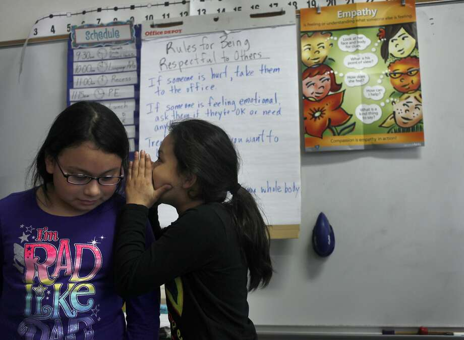 Alexandra Vado (right) whispers into Hannaiz Elia's ear a sentence that was started by their fourth-grade teacher and recited around the circle in a listening exercise at Lakeshore Alternative Elementary School in S.F. Photo: Lacy Atkins, The Chronicle