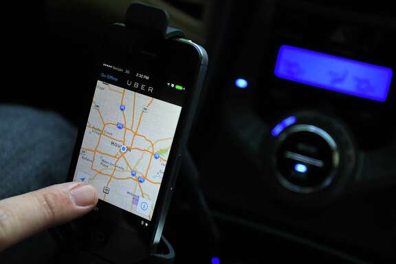 Uber driver Brian Walts locates himself on the Uber map which is part of the ride sharing services that just launched this week on Friday, Feb. 21, 2014, in Houston.