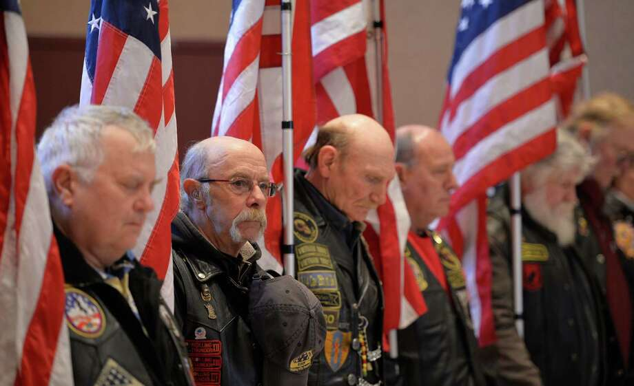 Members of the Patriot Guard bow their heads during the invocation Friday morning, Feb. 20, 2014, during  the opening ceremony of a service which honored veterans of the WWII Pacific Theatre at the Zaloga Post in Albany, N.Y. (Skip Dickstein / Times Union) Photo: SKIP DICKSTEIN / 00025808A