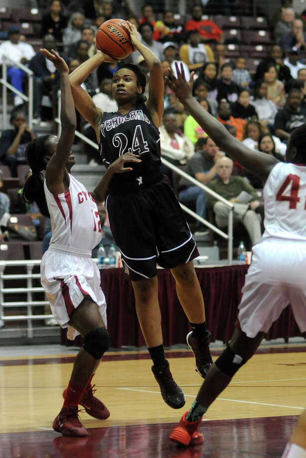 Pearland senior post LaNeetra Guillory (#24) works for a shot between Cy-Woods senior forward Gbemi Orundami, left, and senior forward Olivia Ogwumike during their Region III-5A semifinal playoff at the M.O. Campbell Center on Friday. Photo: Jerry Baker, For The Chronicle
