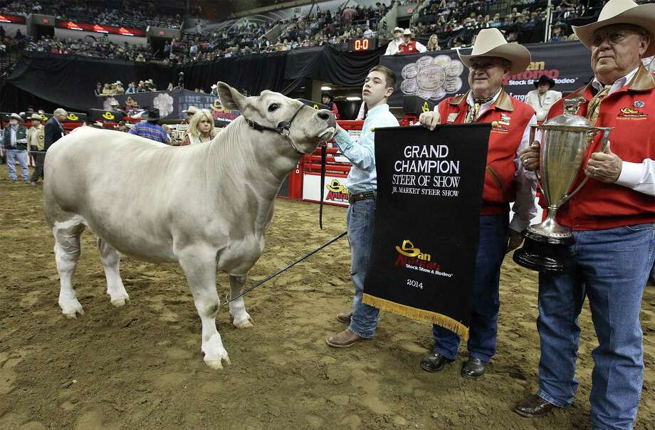 San Antonio Stockshow & Rodeo president Joe Hutchison (from right) holds the trophy and chairman Joe Soules holds the grand champion banner for Braeden Brooks Raub of Lampasas FFA and his All Other Breeds (AOB) steer, Beaner, that took the top prize at the Grand Champion Steer judging at the 2014 San Antonio Stockshow & Rodeo at the AT&T Center on Friday, Feb. 21, 2014. Beaver was selected as the grand champion winner over 1,419 other animals in this year's competition. Photo: Kin Man Hui, San Antonio Express-News / ©2013 San Antonio Express-News