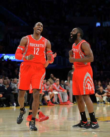 Dwight Howard, left, and guard James Harden reach a high point against the Lakers that proved short-lived as Harden was hurt in an overtime loss the next day. Photo: Mark J. Terrill, STF / AP