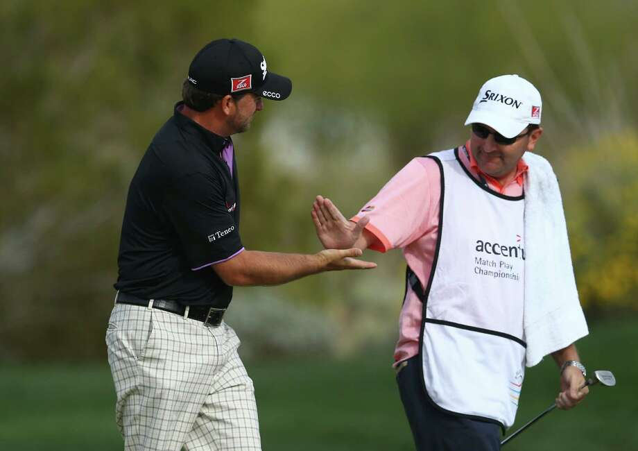 Graeme McDowell, left, celebrates with caddie Ken Comboy after McDowell won the 18th hole to extend his match against Hunter Mahan at the Match Play Championship in Marana, Ariz. McDowell went on to win on the 21st hole and advance to the quarterfinals. Photo: Andy Lyons, Staff / 2014 Getty Images