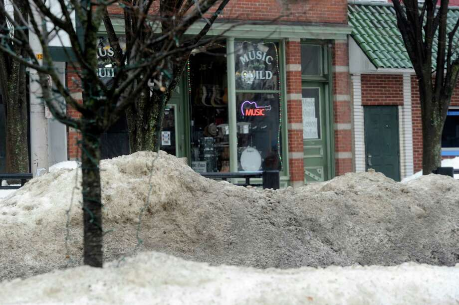 Snow sits in piles on the sidewalk in front of a store on Main Street in Danbury. Merchants and business owners on Main Street are complaining that huge mounds of snow still on the sidewalks are hindering business. Photo: Carol Kaliff / The News-Times