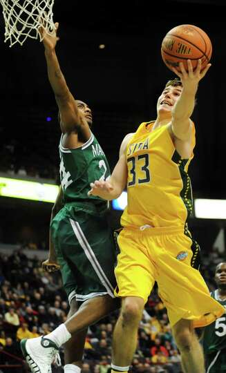 Siena's Rob Poole, right, goes to the hoop as Manhattan's George Beamon defends during their basketb