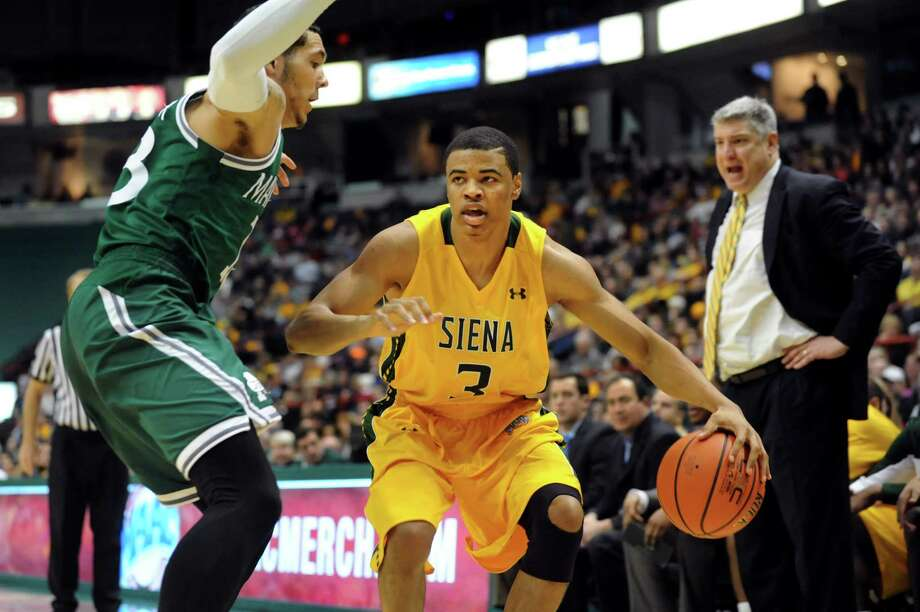 Siena's Ryan Oliver, right, controls the ball as Manhattan's Emmy Andujar defends during their basketball game on Friday, Feb. 21, 2014, at Times Union Center in Albany, N.Y. (Cindy Schultz / Times Union) Photo: Cindy Schultz / 00025724A