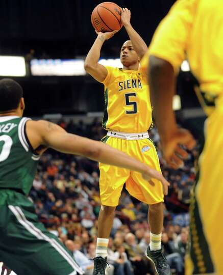 Siena's Evan Hymes, center, shoots for three points during their basketball game against Manhattan o