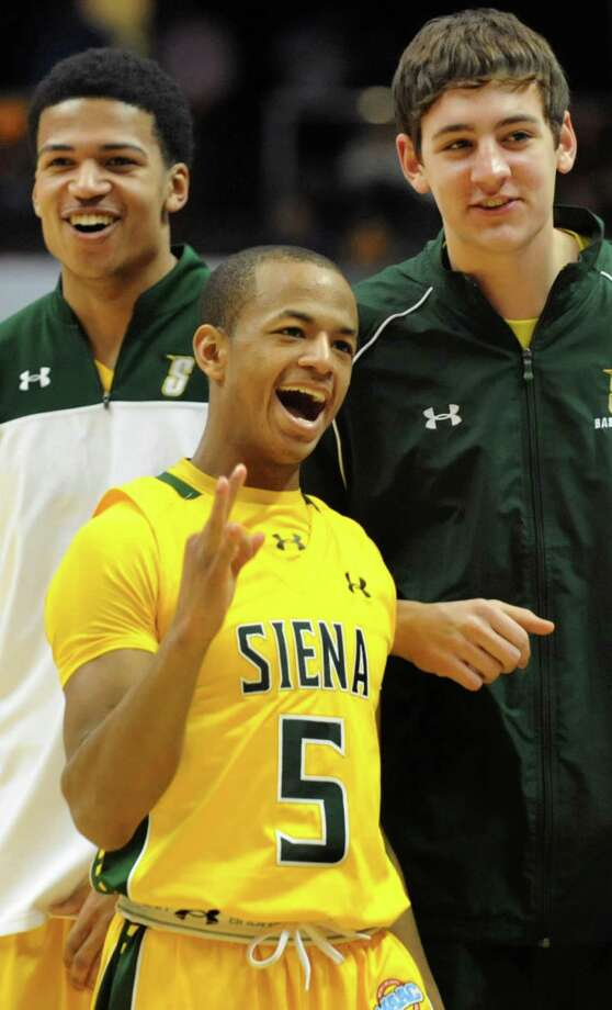 Siena's Evan Hymes, center, celebrates when teammate Ryan Oliver, not pictured, hits two three-point shots to make the score 60-54 during their basketball game against Manhattan on Friday, Feb. 21, 2014, at Times Union Center in Albany, N.Y. Joining Hymes are teammates Michael Wolfe, left, and Jimmy Merrill. (Cindy Schultz / Times Union) Photo: Cindy Schultz / 00025724A