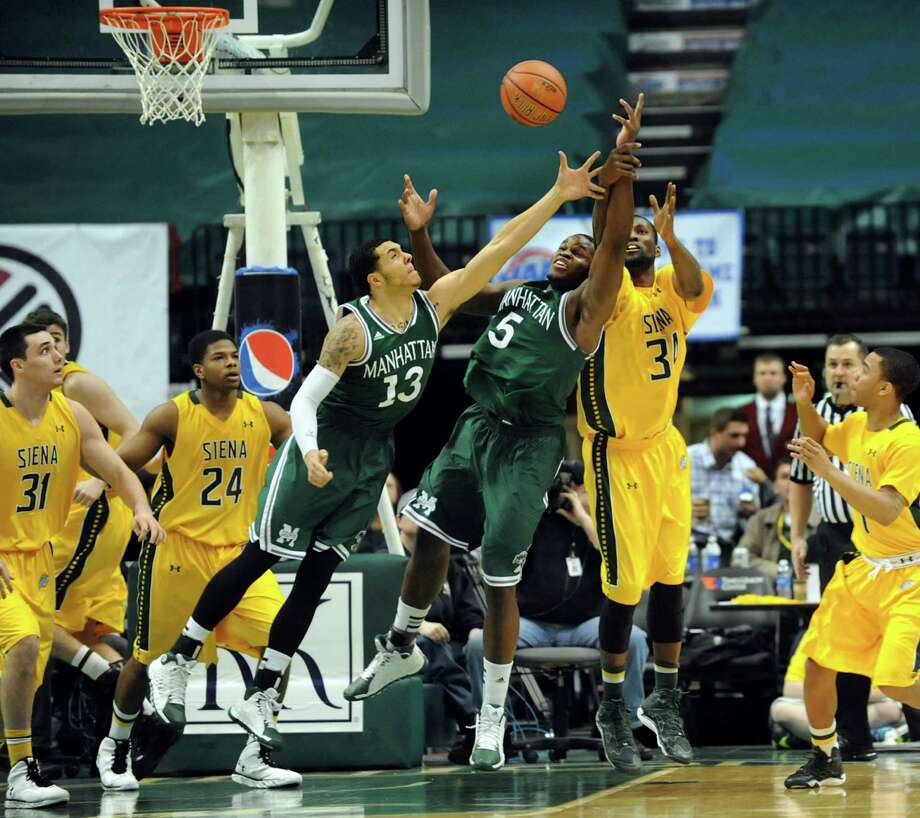 Siena's Imoh Silas, right, battles for a rebound with Manhattan's Emmy Andujar, third from left, and Rhamel Brown during their basketball game on Friday, Feb. 21, 2014, at Times Union Center in Albany, N.Y. (Cindy Schultz / Times Union) Photo: Cindy Schultz / 00025724A