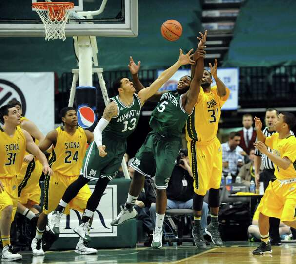 Siena's Imoh Silas, right, battles for a rebound with Manhattan's Emmy Andujar, third from left, and