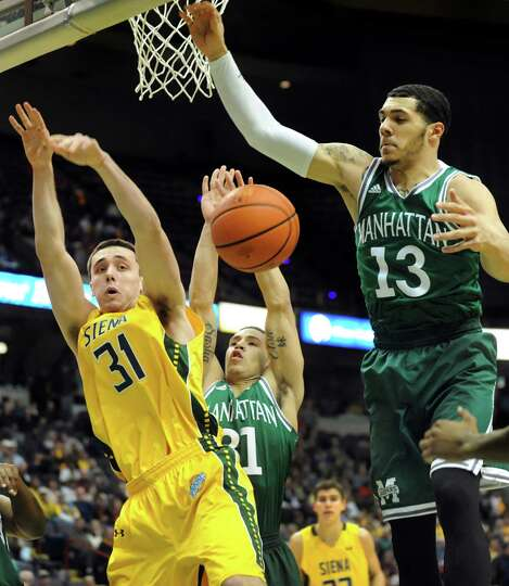 Siena's Brett Bisping, left, battles for a rebound with Manhattan's Michael Alvarado, center, and Em
