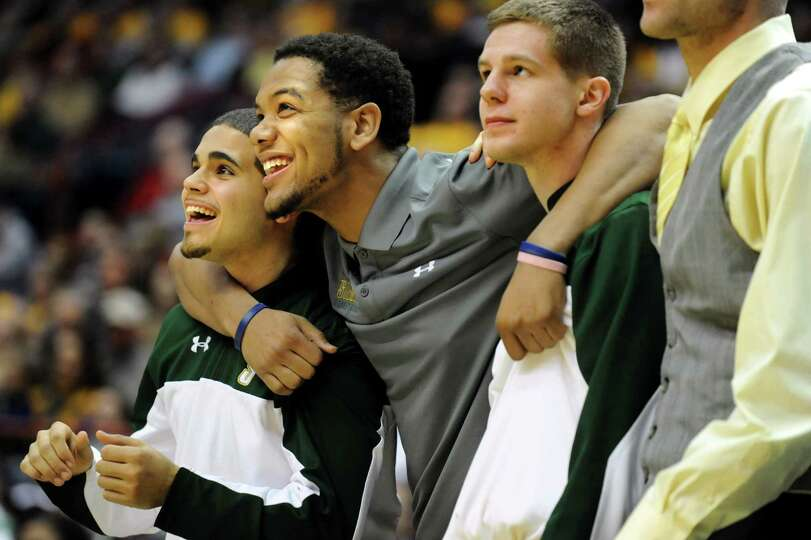 Siena's Steven Cruz, left, Patrick Cole and Mike Wilson watch with anticipation as Rob Poole shoots