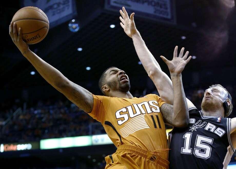 Phoenix Suns' Markieff Morris (11) tries to get off a shot over San Antonio Spurs' Matt Bonner (15) during the first half of an NBA basketball game, Friday, Feb. 21, 2014, in Phoenix. (AP Photo/Ross D. Franklin) Photo: Associated Press