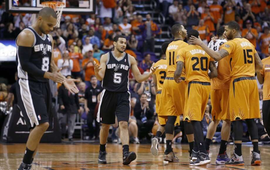 San Antonio Spurs' Patty Mills (8), of Australia, and Cory Joseph (5) walk back to the team bench as Phoenix Suns' Marcus Morris (15), Archie Goodwin (20), Markieff Morris (11) and Ish Smith (3) celebrate a score by Goodwin during the second half of an NBA basketball game, Friday, Feb. 21, 2014, in Phoenix. The Suns defeated the Spurs 106-85. (AP Photo/Ross D. Franklin) Photo: Associated Press