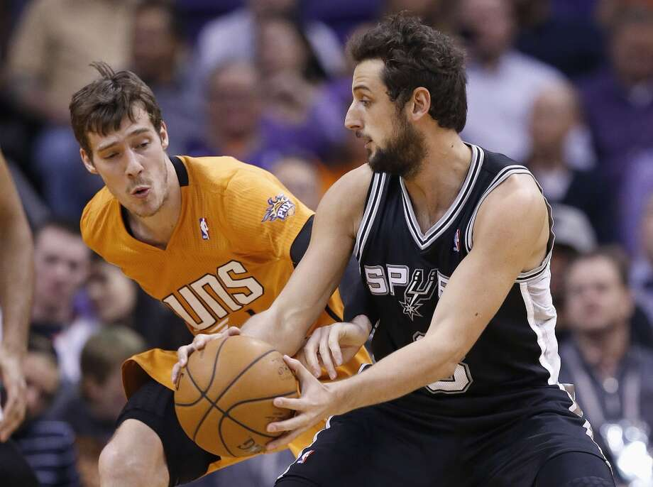 Phoenix Suns' Goran Dragic, left, of Slovenia, reaches for the basketball as he tries to knock the ball away from San Antonio Spurs' Marco Belinelli, right, of Italy, during the first half of an NBA basketball game, Friday, Feb. 21, 2014, in Phoenix. (AP Photo/Ross D. Franklin) Photo: Associated Press