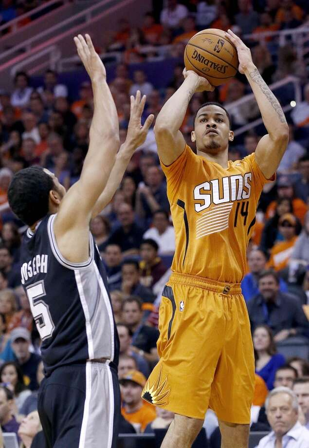 Phoenix Suns' Gerald Green (14) gets off a shot over the defense of San Antonio Spurs' Cory Joseph (5) during the first half of an NBA basketball game, Friday, Feb. 21, 2014, in Phoenix. (AP Photo/Ross D. Franklin) Photo: Ross D. Franklin, Associated Press
