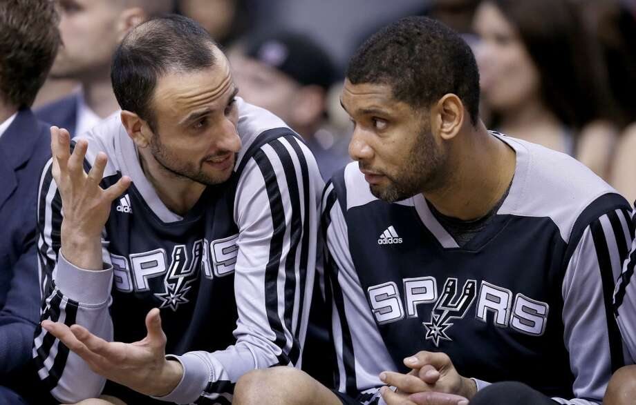 San Antonio Spurs' Manu Ginobili, left, and Tim Duncan talk as they spend most of the second half of an NBA basketball game against the Phoenix Suns on the bench, Friday, Feb. 21, 2014, in Phoenix. The Suns defeated the Spurs 106-85. (AP Photo/Ross D. Franklin) Photo: Ross D. Franklin, Associated Press