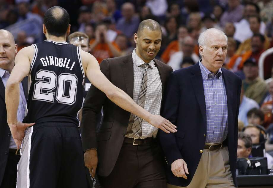 San Antonio Spurs coach Gregg Popovich, right, is escorted back to the bench by assistant coach Ime Udoka, second from right, as they walk past Manu Ginobili (20), of Argentina, who holds out his hand, after Popovich was called for a technical foul during the first half of an NBA basketball game against the Phoenix Suns, Friday, Feb. 21, 2014, in Phoenix. (AP Photo/Ross D. Franklin) Photo: Associated Press