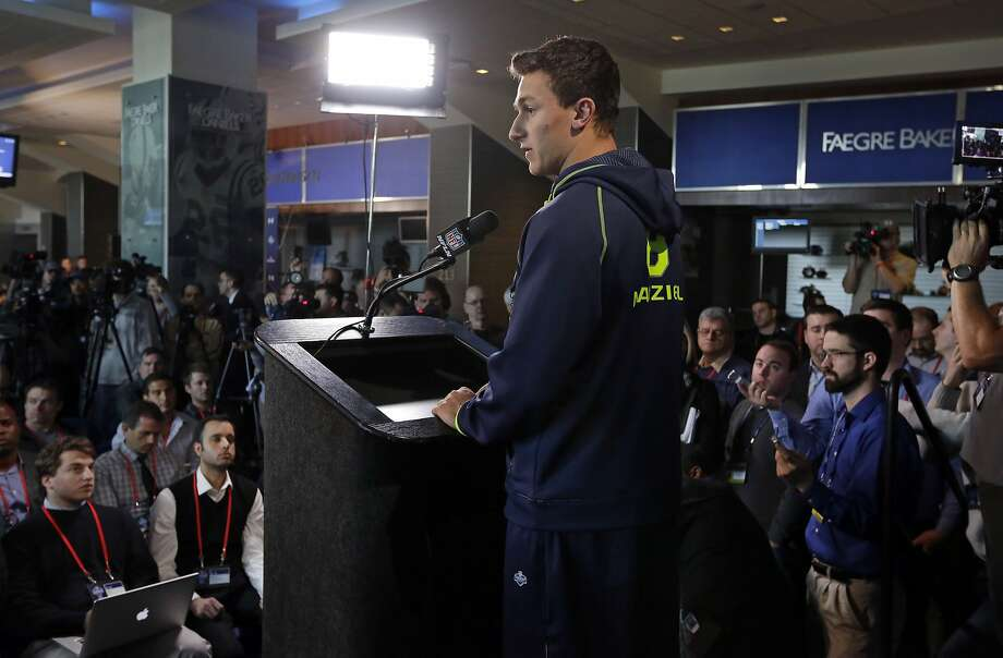Texas A&M quarterback Johnny Manziel is surrounded by the media as answers a question during a news conference at the NFL football scouting combine in Indianapolis, Friday, Feb. 21, 2014. (AP Photo/Michael Conroy) Photo: Michael Conroy, Associated Press