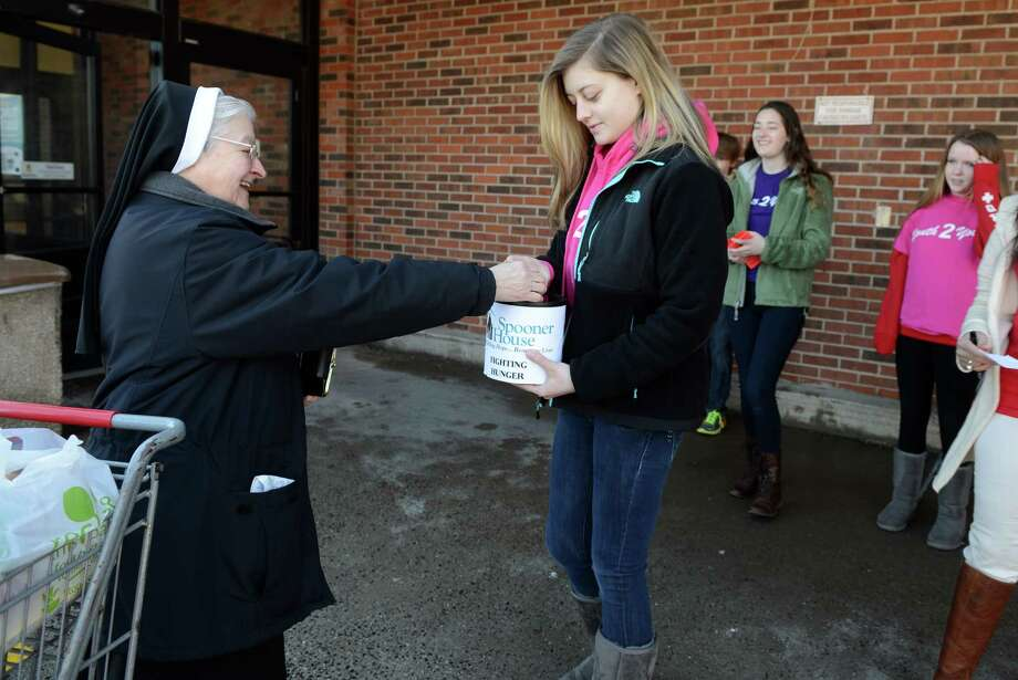 Emma White, 16, of Shelton, collects a donation from Sister Ruth Aubrey, of St. Joseph Church in Shelton, for the Spooner House Saturday, Feb. 22, 2014, at the Stop and Shop store in Shelton, Conn. during the 12th annual Valley Has a Heart food drive.  Youth 2 Youth members, and other volunteers, were collecting non-perishable items and money to use for restocking the food bank shelves as needed during the cold winter months. Photo: Autumn Driscoll / Connecticut Post
