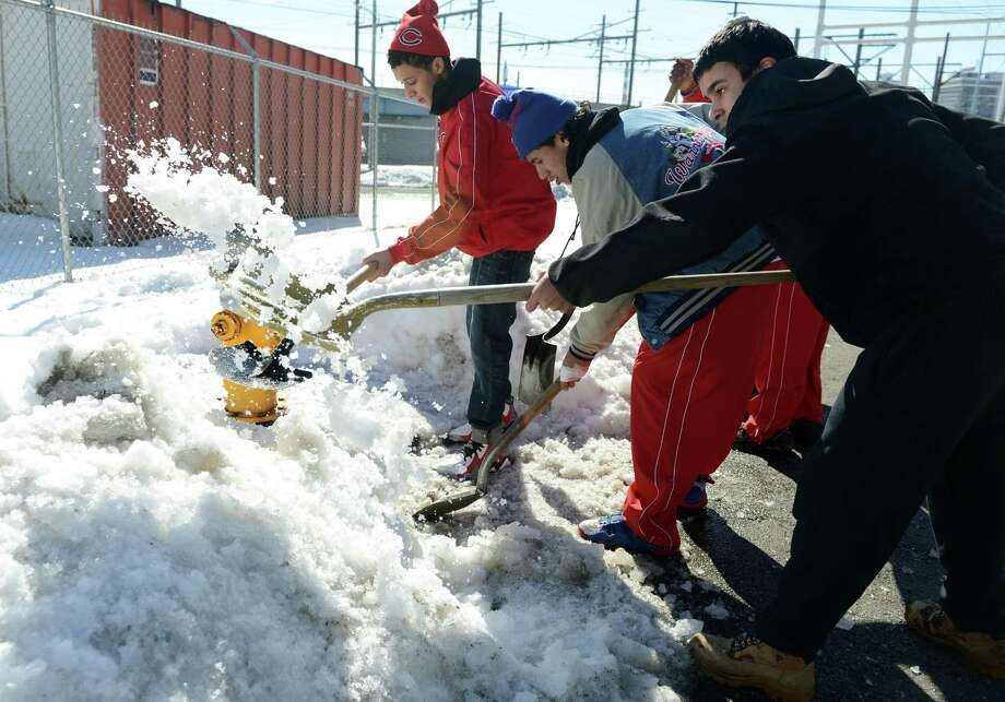 American Legion baseball players, from left, Darryl Belton, 15, Juan DeLaRosa, 15, and Jacob Lugo, 15, shovel snow around a fire hydrant on Harriet Street in Bridgeport, Conn. Saturday, Feb. 22, 2014. Photo: Autumn Driscoll / Connecticut Post