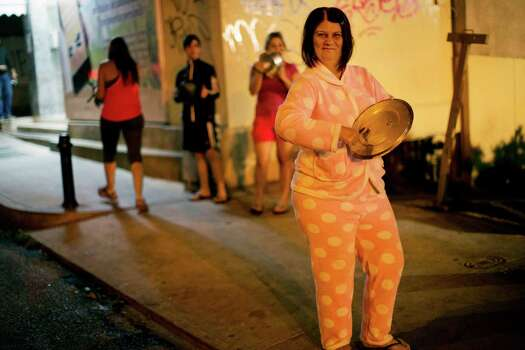 A woman wearing her pajamas bangs on a pot during an anti-government demonstration in the Altamira neighborhood of Caracas, Venezuela, Friday, Feb. 21, 2014. The anti-government movement has appeared to have snowballed into a political crisis, the likes of which Venezuela's socialist leadership hasn't seen since a 2002 coup attempt. Protest rallies are expected throughout the country on Saturday. Photo: Rodrigo Abd, AP / AP