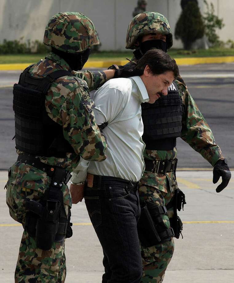 """Joaquin """"El Chapo"""" Guzman is escorted to a helicopter in handcuffs by Mexican navy marines at a navy hanger in Mexico City,  Mexico, Saturday, Feb. 22, 2014. A senior U.S. law enforcement official said Saturday, that Guzman, the head of Mexico's Sinaloa Cartel, was captured alive overnight in the beach resort town of Mazatlan. Guzman faces multiple federal drug trafficking indictments in the U.S. and is on the Drug Enforcement Administration's most-wanted list.  (AP Photo/Eduardo Verdugo) Photo: Eduardo Verdugo, Associated Press / AP"""