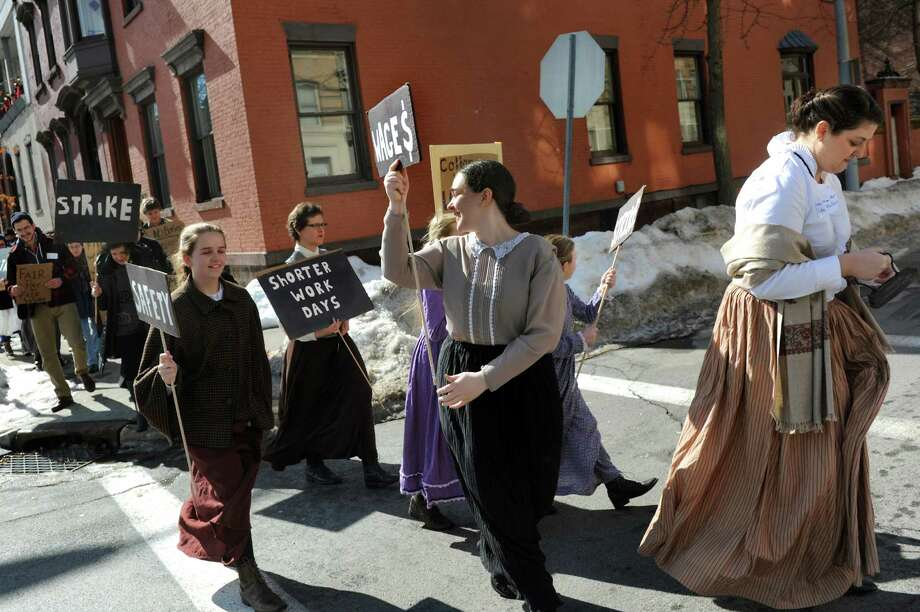 Brandishing an iron, Ilene Frank, executive director at Rensselaer County Historical Society, right, leads a walk from RCHS to the Troy Farmers Market on Saturday, Feb. 22, 2014, in Troy, N.Y. The walk commemorated the 150th anniversary of Kate Mullany's historic formation of the Collar Laundry Union in Troy. Mullany organized 300 of her fellow laundry workers to strike for higher wages and improved working conditions in the collar laundries. (Cindy Schultz / Times Union) Photo: Cindy Schultz / 00025852A