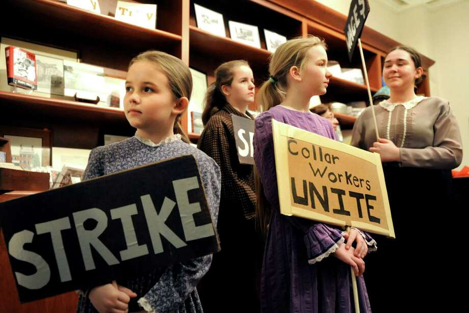 Participants hold their signs as they gather for a walk to the Troy Farmers Market on Saturday, Feb. 22, 2014, at Rensselaer County Historical Society in Troy, N.Y. From left, are sisters Katherine Desrosiers, 8, Regina Desrosiers, 13, and Therese Desrosiers, 10, all of Coxsackie, and Deborah Brannan, 15, of Catskill. The walk commemorated the 150th anniversary of Kate Mullany'€™s historic formation of the Collar Laundry Union in Troy. Mullany organized 300 of her fellow laundry workers to strike for higher wages and improved working conditions in the collar laundries. (Cindy Schultz / Times Union) Photo: Cindy Schultz / 00025852A