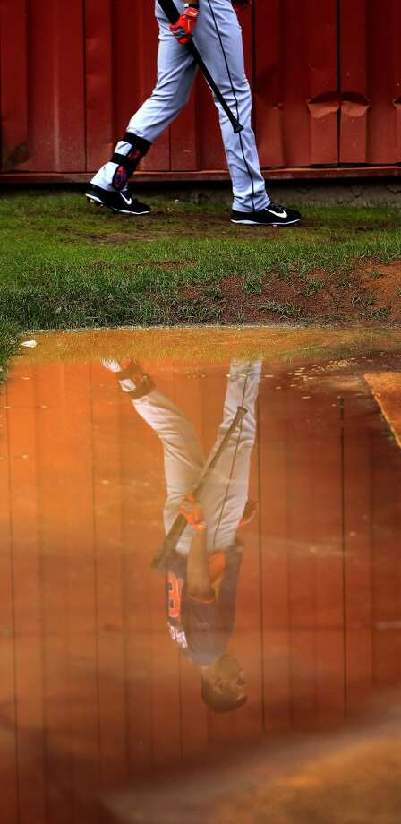 Carlos Correa of the Astros walks past a puddle after a brief rain storm during spring training workouts. Photo: Karen Warren, Houston Chronicle