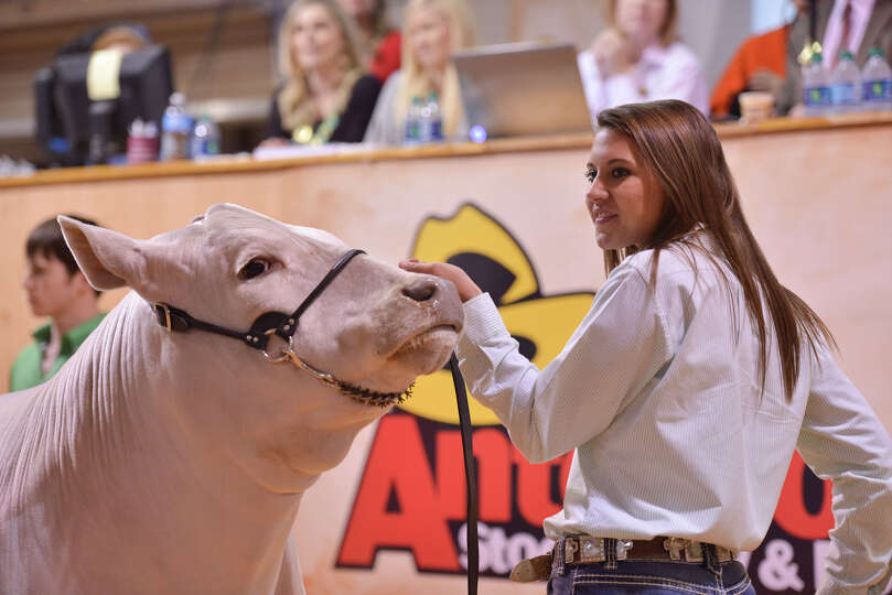 Ashley Bradley holds her reserve grand champiion during the San antonio Stock Show and Rodeo Auction