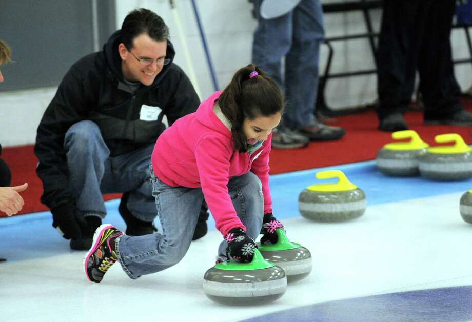 Seven-year-old Marisil Van Slyke is watched by her dad, Chip Van Slyke, of Glenville as she gets an introduction to curling during the Schenectady Curling Club open house on Saturday Feb. 22, 2014 in Niskayuna, N.Y. (Michael P. Farrell/Times Union) Photo: Michael P. Farrell / 00025850A