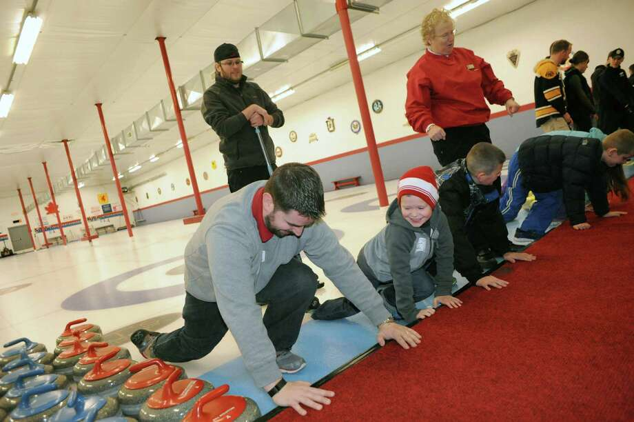 Dan O'Brien of Niskayuna, left, and his six-year-old son, Patrick O'Brien, learn the curling warm up during the Schenectady Curling Club open house on Saturday Feb. 22, 2014 in Niskayuna, N.Y. (Michael P. Farrell/Times Union) Photo: Michael P. Farrell / 00025850A