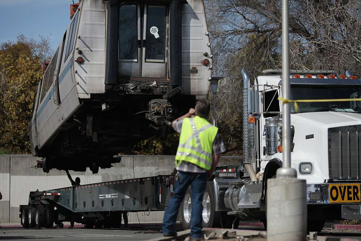 Workers stead a Bart train as it is lowered on a truck to be taken off in Concord, Calif. on Saturday, Feb. 22, 2014. A train derailed near the Concord Bart Station late Friday night.