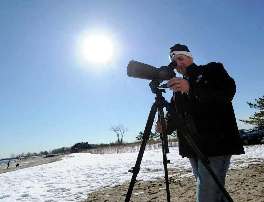 Using a telescope, Jason Rieger of Wallingford, Conn., a Connecticut Ornithological Association member, takes advantage of the mild weather in an attempt to spot the Eared Grebe, a water bird not normally seen in this area Rieger said, at Greenwich Point, Saturday afternoon, Feb. 22, 2014. Photo: Bob Luckey / Greenwich Time