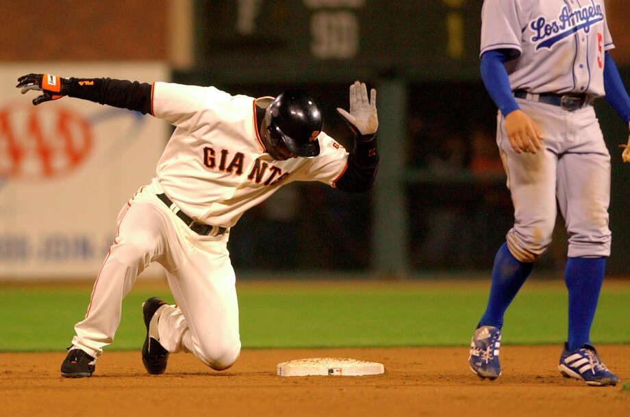 San Francisco Giants' Barry Bonds slaps the second base bag after successfully recording his 500th career stolen base as Los Angeles Dodgers second baseman Jason Romano stands by during the 11th inning Monday, June 23, 2003 in San Francisco. Bonds became the first player ever with 500 stolen bases and 500 home runs. Photo: Julie Jacobson, AP / AP