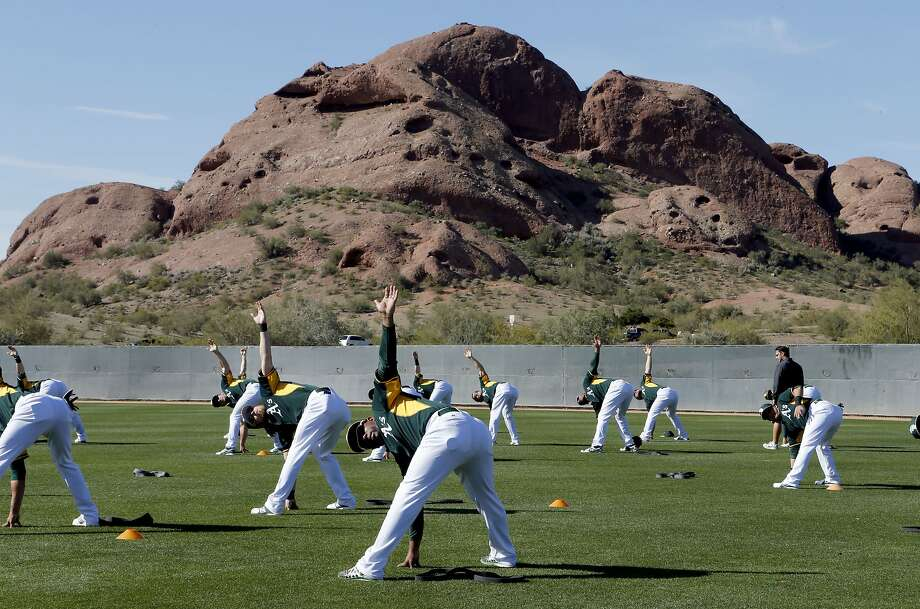 The A's warm up during spring training at the Papago Baseball Complex in Phoenix, but with several weeks of the same ahead, everyone's looking for different stories. Photo: Michael Macor, The Chronicle