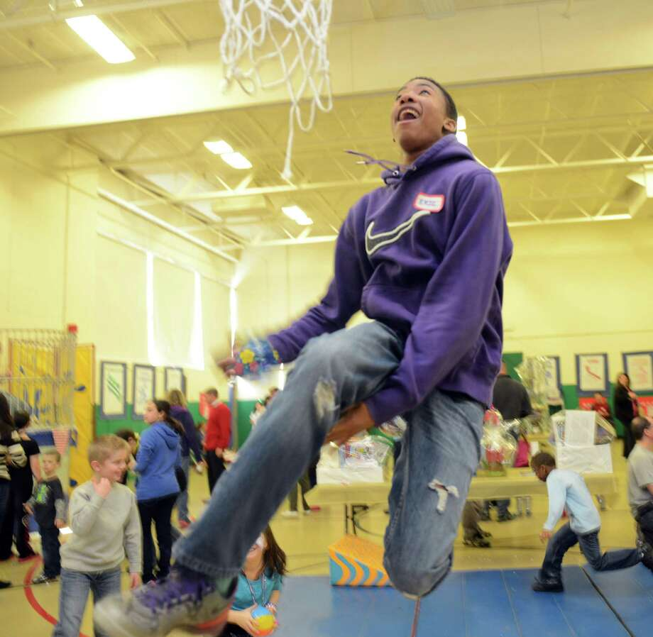 "Eric Hicks, 17, a Derby High School basketball player, shows off his skills Saturday, Feb. 22, 2014, during ""The Olympics"" Fun Fair in the gym at Bradley School in Derby, Conn. Photo: Autumn Driscoll / Connecticut Post"
