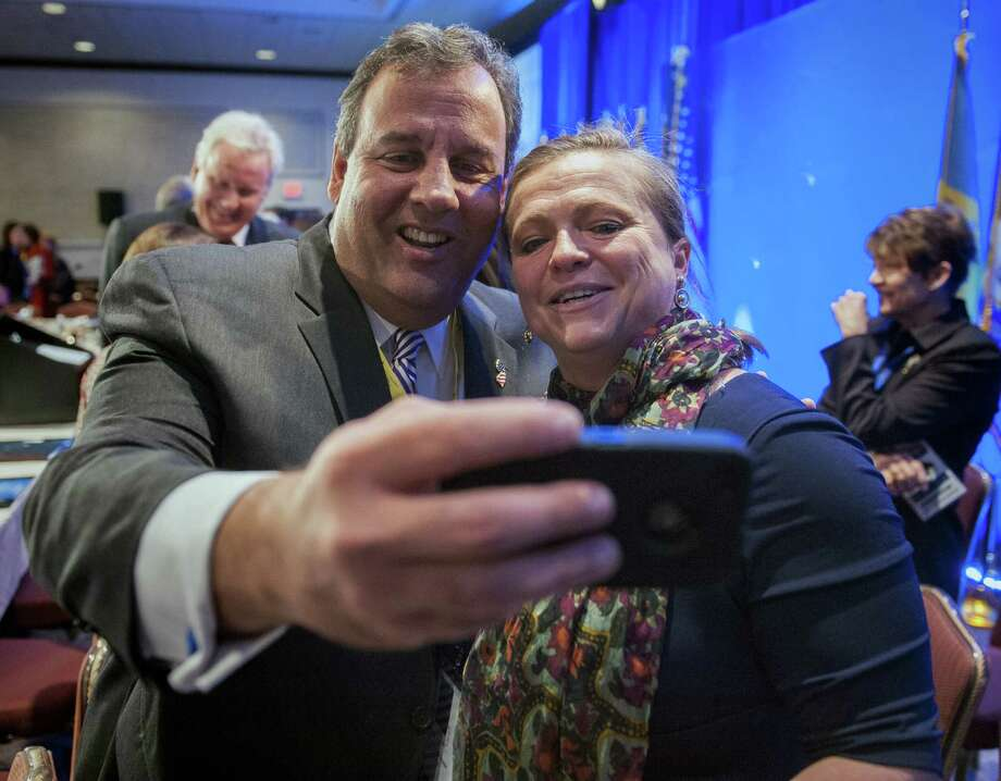 New Jersey Gov. Chris Christie takes a cell phone photo with NGA staffer Lily Kersh of Little Rock, Ark., during the National Governor's Association Winter Meeting in Washington, Saturday, Feb. 22, 2014. (AP Photo/Cliff Owen) Photo: Cliff Owen, FRE / FR170079 AP