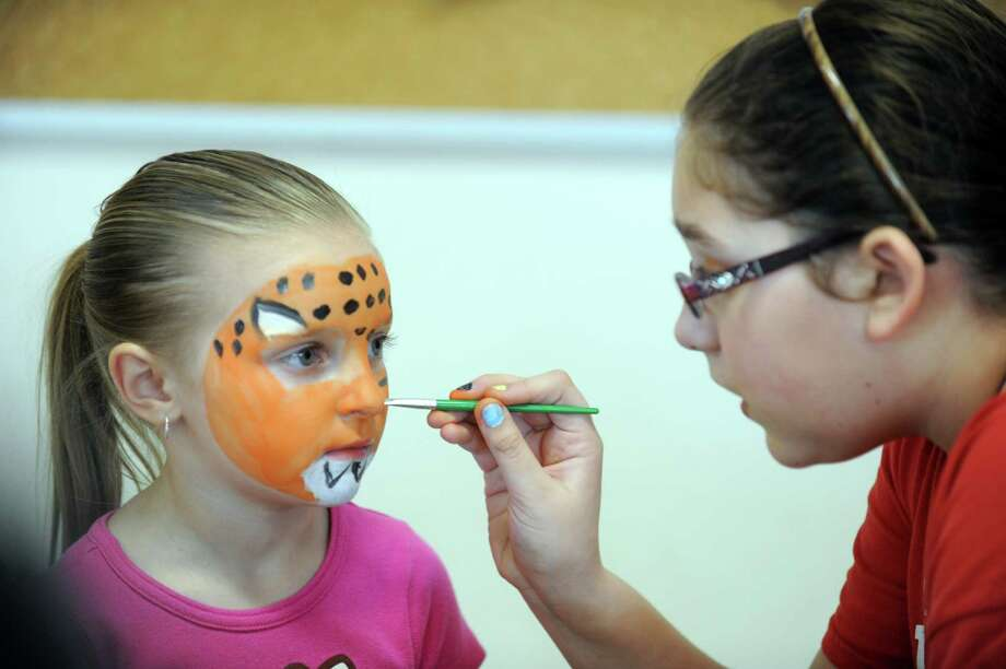 "Rachel Gall, 11, of Derby, transforms 5-year-old Emily Caron, of Derby, into a cheetah Saturday, Feb. 22, 2014, during ""The Olympics"" Fun Fair in the gym at Bradley School in Derby, Conn. Photo: Autumn Driscoll / Connecticut Post"