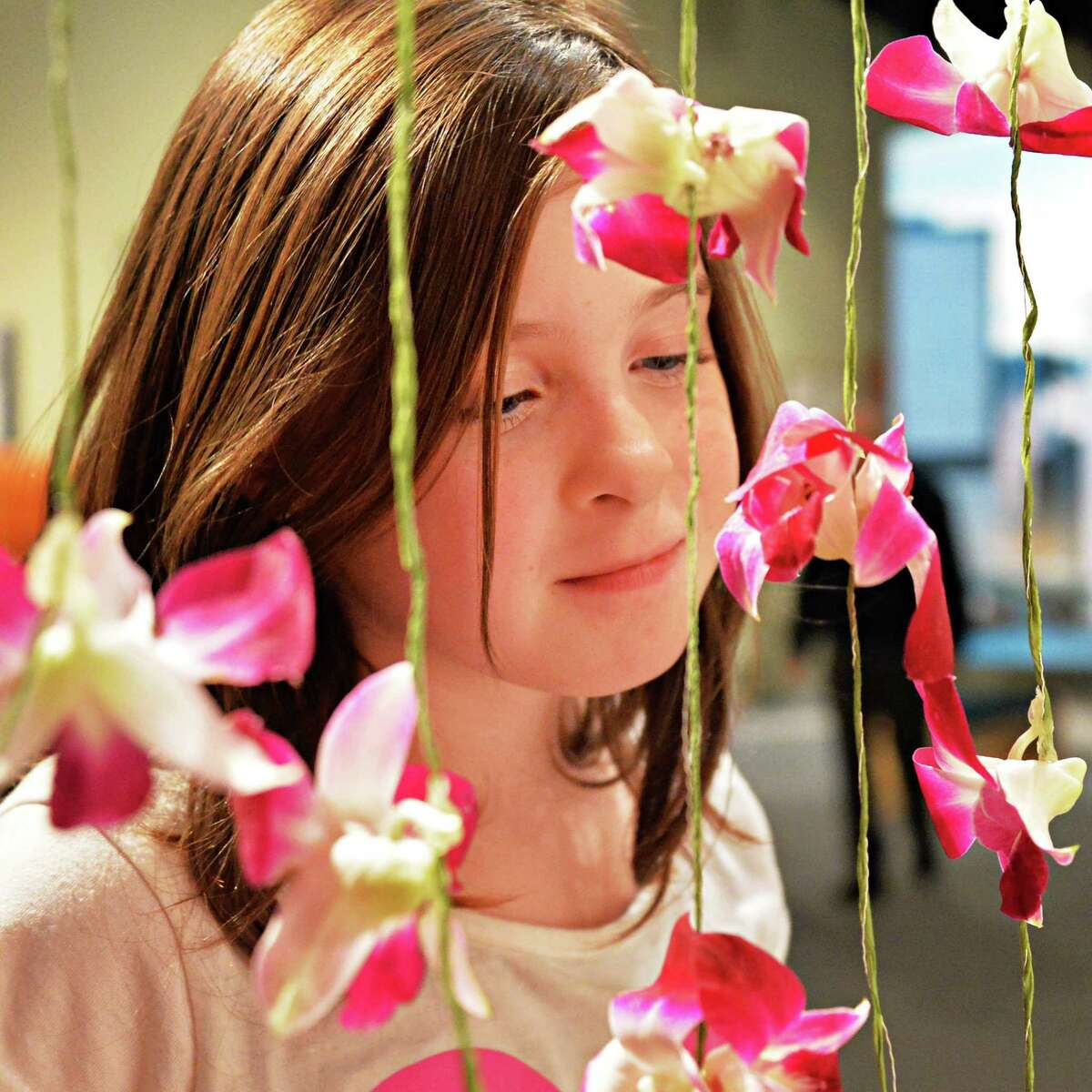 Eight-year-old Hannah Eamer-Dulin of Richmondville smells an orchid at the New York in Bloom annual fundraiser for educational programs for children at the New York State Museum Saturday Feb. 22, 2014, in Albany, NY. (John Carl D'Annibale / Times Union)