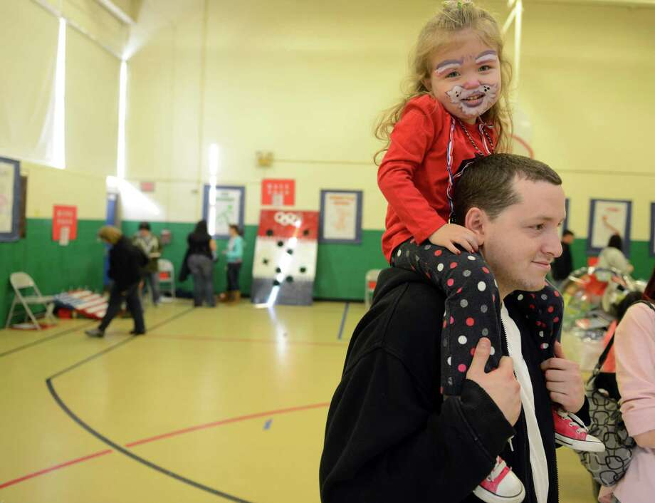 "Three-year-old Dakota Cottrell sits on her father Matthew's shoulders Saturday, Feb. 22, 2014, during ""The Olympics"" Fun Fair in the gym at Bradley School in Derby, Conn. Photo: Autumn Driscoll / Connecticut Post"
