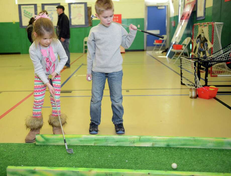 "Seven-year-old Casey Fish, of Derby, watches Kaelyn DiMartino, 7, of Derby, take her shot as they play golf Saturday, Feb. 22, 2014, during ""The Olympics"" Fun Fair in the gym at Bradley School in Derby, Conn. Photo: Autumn Driscoll / Connecticut Post"