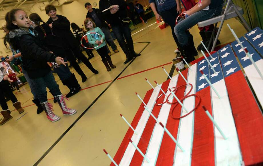 "Eight-year-old Kayla McKenzie, of Beacon Falls, plays ring toss Saturday, Feb. 22, 2014, during ""The Olympics"" Fun Fair in the gym at Bradley School in Derby, Conn. Photo: Autumn Driscoll / Connecticut Post"