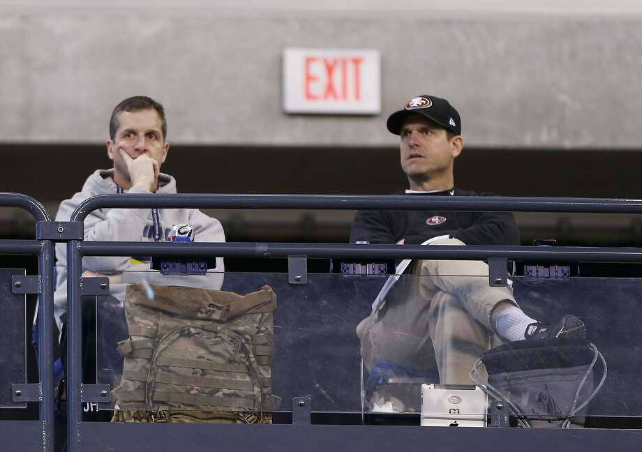 "Niners coach Jim Harbaugh (right), sitting with his brother, Ravens coach John Harbaugh, at the combine, calls reports that he was nearly traded ""ridiculous."" Photo: Brian Spurlock, Reuters"