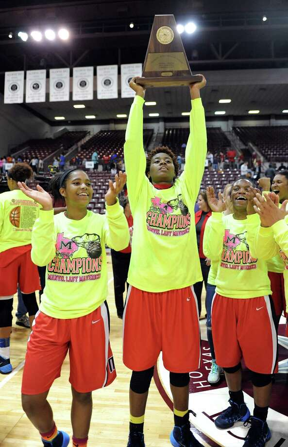 Manvel's Jordan Hosey, center, lifts the Region 3 champion's trophy after the Lady Mavericks defeated Cy-Woods, 58-42 in the Class 5A Region 3 Final girls high school basketball game, Saturday, February 22, 2014, at Campbell Center in Houston. Photo: Eric Christian Smith, For The Chronicle