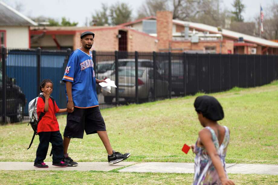 Jimmy Coffman walks with his daughter, Aaniyah Neal, 5, from Nathaniel Q. Henderson Elementary, which is slated for closure. Photo: Brett Coomer, Staff / © 2014 Houston Chronicle